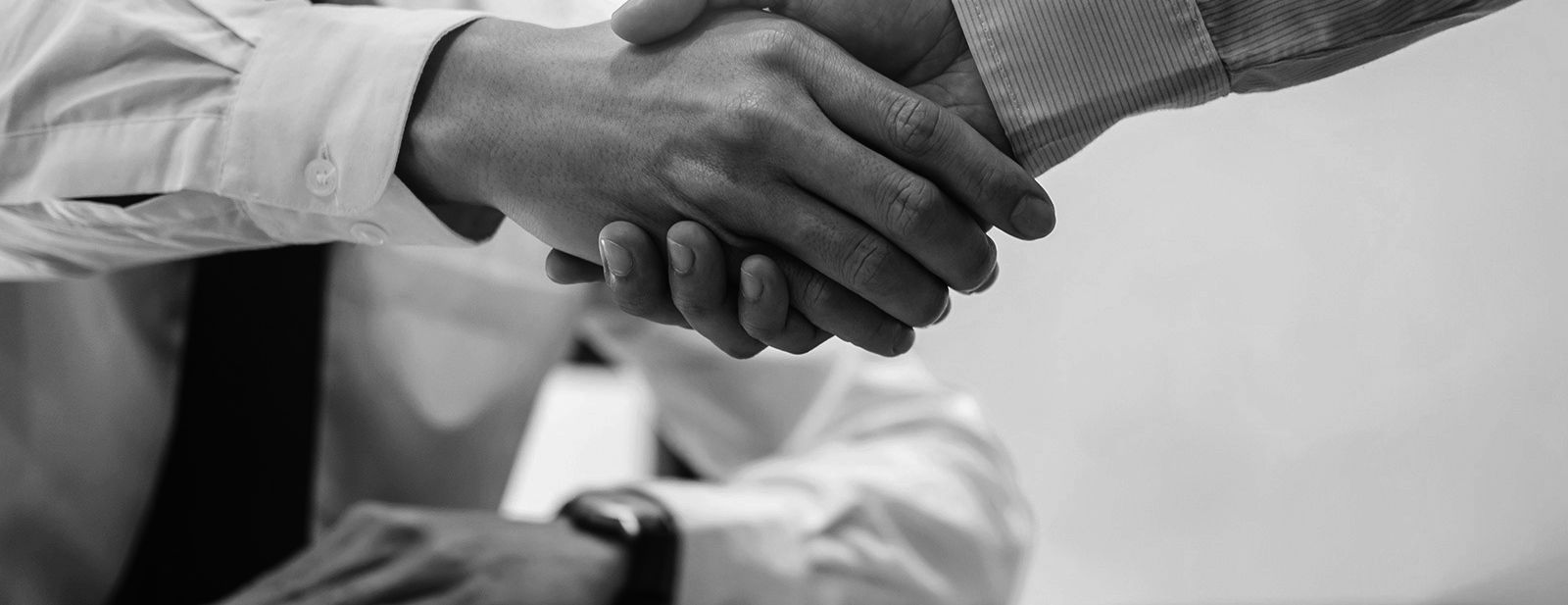Broker agent and customer shaking hands after signing contract documents.